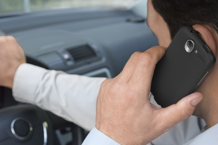 mobile telephones: Man phones while driving a car