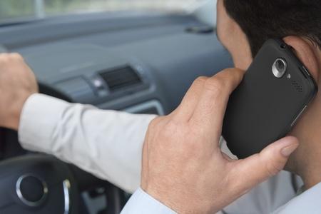 hombre manejando: Tel�fonos hombre mientras se conduce un coche Foto de archivo