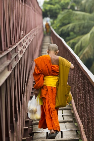 buddhist monk: Young monk returns from shopping Stock Photo
