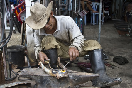 CAMBODIA - NOV 26:  Welder in a garage working on a motorcycle axis. Due to the large november heat many workers relocate their workplace outdoors.  Cambodia in November 26, 2011