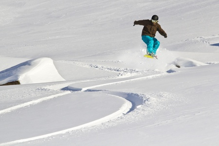 Snowboarder uses snowcovered rock for a jump Banque d'images