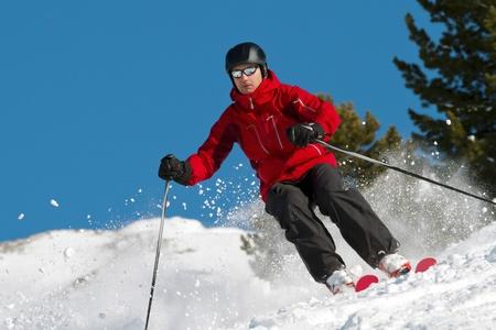 男性は新鮮な粉でスキーします。