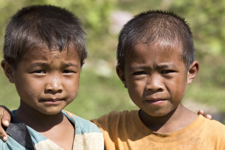 LAOS - NOVEMBER 13: Laos is one of the poorest countrys of the world with an income per head of 390 US Dollar in the year. Forty percent of the children never visit a school. Unknown Laos friends posing for photo  2011 in Vang Vieng, Laos.