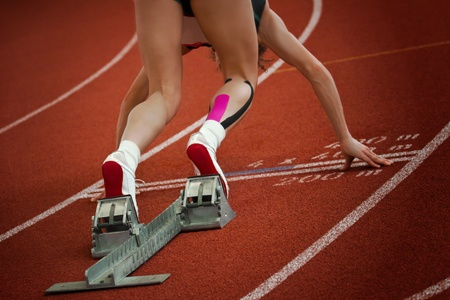 gravity: Female short distance runner on gravity slope curve is in start position Stock Photo