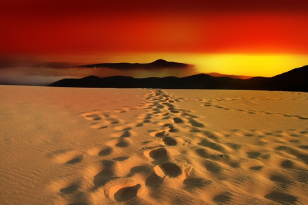 red mountain: Glowing sundown in the desert with footsteps in the sand Stock Photo