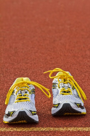 Vertical picture of a pair of runners on red tartan surface photo