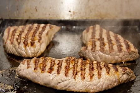 marmorate: Tre bistecche sulla griglia industriale