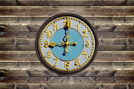 Wooden clock face on rustic wood board photo