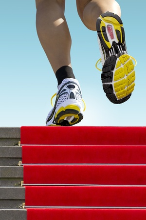 the runs: Athlete on red carpet runs up the stairs Stock Photo