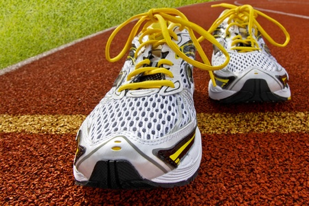 Pair of sports shoes standing on a tartan race track photo