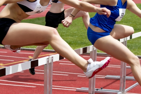 Female sprinter leaping over hurdles photo