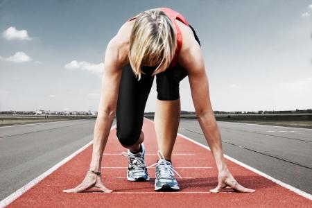 startpunt: Vrouw sprinter wachten voor de start op een vliegveld landingsbaan