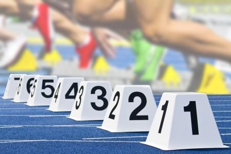 atletismo: cubos de partida con escena de inicio en el fondo Foto de archivo