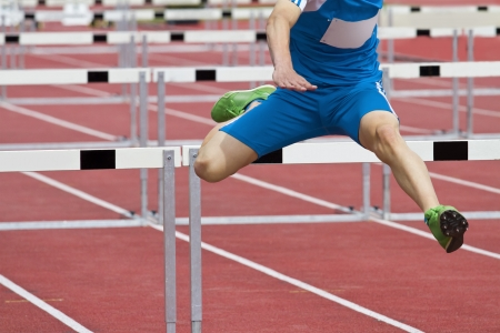track and field athlete: hurdle runner leaping over the hurdles