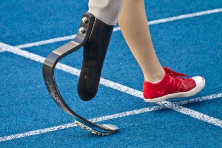 ハンディキャップを持つ女性の運動選手がゴールラインします。