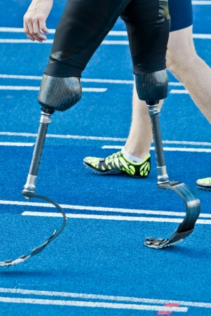 athlete with handicap walks racetrack with non-disabled athlete Stock Photo