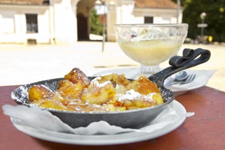 Austrian and bavarian dessert speciality  Kaiserschmarrn  with apple juice in the original environment of a castle courtyard Stock Photo