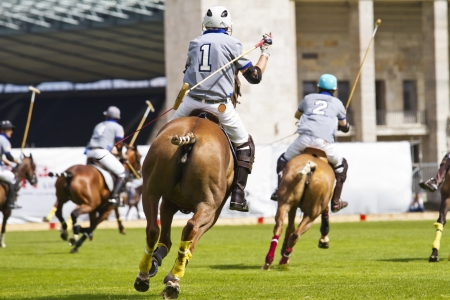 Rear view of riding polo player in a match