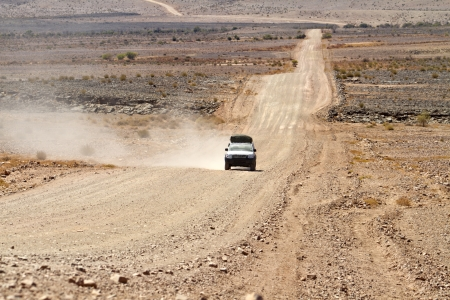 lonely road: SUV with tourists traveling in Namibia Editorial