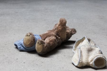 Despojado de peluche con el brazo levantado sobre suelo de hormig�n Foto de archivo