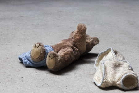 Stripped teddy with raised arm on concrete floor Standard-Bild