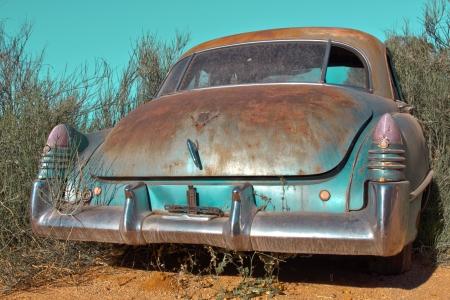 Oldtimer coche de pie en el arbusto Foto de archivo