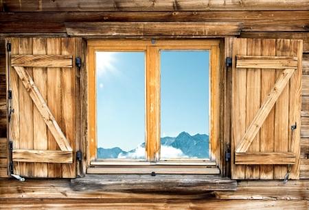 Verwitterte Fassade einer Berghütte mit Berg Spiegelbild im Fenster Lizenzfreie Bilder