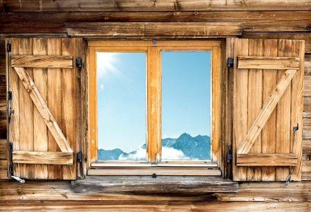 Weathered facade of a mountain hut with mountain  reflection in the window Фото со стока