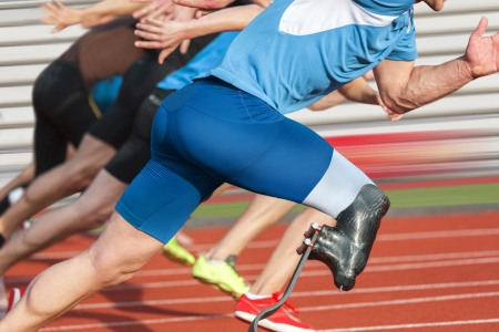 Handicapped sprinter starts short track race with unhindered athletes Banque d'images