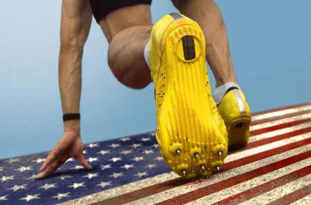 Sprinter with spikes is in start position on  grungy US flag photo