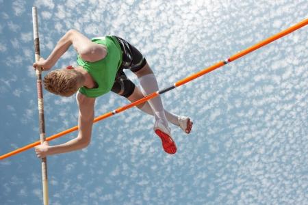 Jonge atleten polsstokhoogspringen lijkt de hemel te bereiken Stockfoto