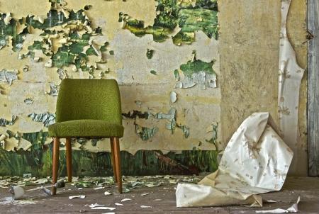 Silla vieja se pone delante de un copos de pared Foto de archivo