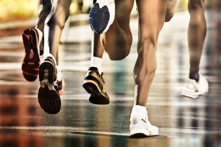 atletisch: Lopers op natte grond met de stad reflectie