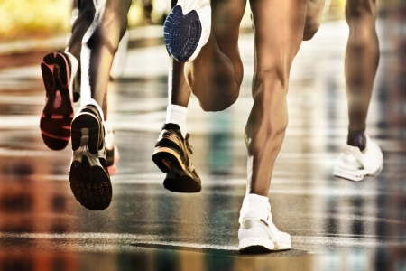 Runners on wet ground with city reflection photo