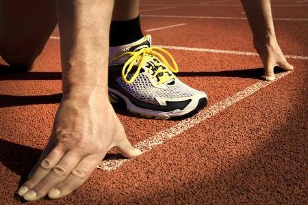 coureur: Runner dans un stade est en position de d�part avec les mains sur la ligne