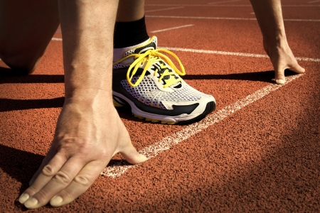 Runner in a stadium is in start position with hands on the line Фото со стока