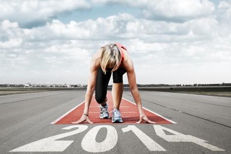 Sprinter sexo femenino que espera para el inicio de una pista de aterrizaje en la vista en perspectiva en primer plano de las letras 2014