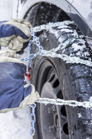 mounts: Car driver mounts snow chains on the tyre of his car
