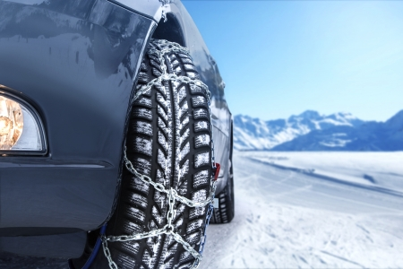 wintry: Car with mounted snow chains in wintry environment