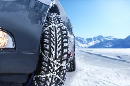 Coche con cadenas para la nieve montadas en el ambiente invernal Foto de archivo - 25325843