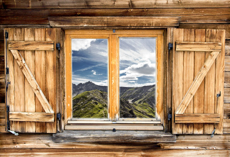 mountain hut: Weathered facade of a mountain hut with summer mountain reflections