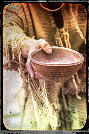 tattered: Medieval beggar holds out his wooden cup to ask for money, interpreted as aged picture with singed frame