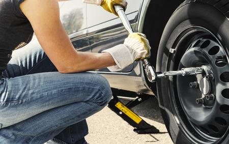 女性は彼女の車のホイール レンチでタイヤを変更します。 写真素材