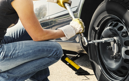 Woman is changing  tire of her car with wheel wrench  Standard-Bild