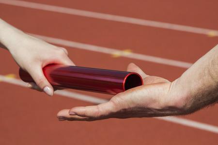carrera de relevos: Atleta femenina manos sobre la barra de la carrera de relevos a un atleta masculino