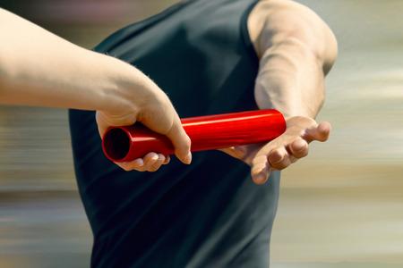 女子リレー ランナーの手赤ポール男性ランナーに