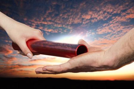 relevos: La hembra da el relevo carrera de relevos a una mano masculina en la puesta del sol