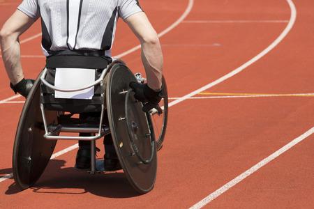 persona en silla de ruedas: Atleta con silla de ruedas se concentra para su carrera al inicio