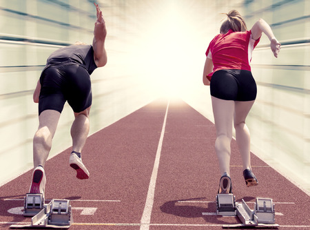 Male and female sprinter starting out of the blocks