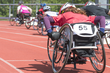 Athletes  at a wheelchair race in a stadium